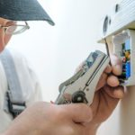 man installing thermostat | thermostat locations | Stiles Heating & Cooling